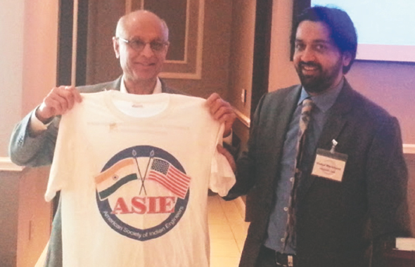 ASIE Member and Past Board Member Chad Patel (left) receives a prize from ASIE President Vishal Merchant.
