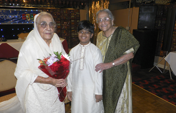 Shakuntla Malhotra (left) and Radha Golikeri pose with Adarsh Suresh, who sang the national anthems.