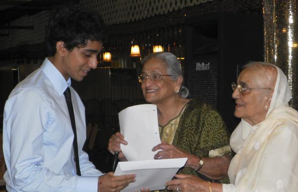 Shakuntla Malhotra gives out the award to Gaurav Dhume as Radha Golikeri (center) looks on.