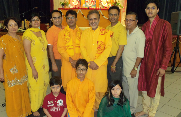 The two visiting Jivandani Karya Kartas or Lifelong Volunteers from the Gayatri Chetna Center in Shantikunj, India Raj Pushkar Singh and Onkar Lal Patidar (with beard) in center with Directors of the Houston Chapter Gayatri Pariwar Chapter, from left Sangeeta Tailor, Trustee; Garima Doshi, Joint Secretary; Ketan Doshi, Secretary; Mahesh Patel President, Bharat Tailor Vice President and Viral Patel, volunteer.  The Tailor's children are seated in front. Treasurer Deepak Khatri was not available for the picture.              		         Photos: Jawahar Malhotra
