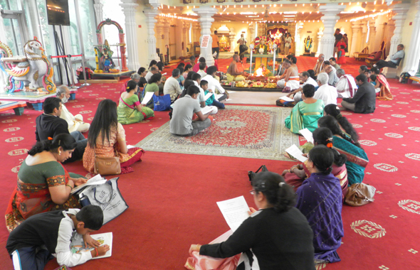 Priests lead a sanctifying puja as the faithful follow along.