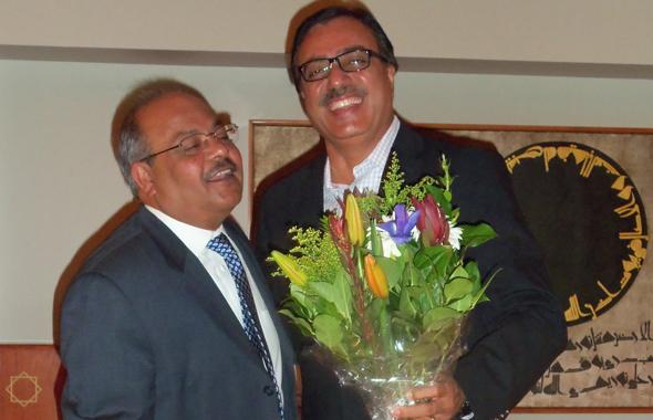 Hussain presenting a bouquet to Jamatkhana President Aftab Ghesani.