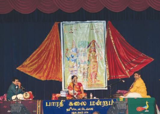 Vishaka Hari (center) with accompanying artists. violinist Ananthakrishnan  and mridangist, Arjun Ganesh, with the backdrop of Sri Meenakshi Kalyanam on stage at MTS.Photos: Dr. Gopal and Dr. Vaduganathan