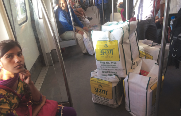 A family transports wedding sarees in the Metro