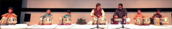 An ensemble of young tabla students are accompanied by Pandit Shantilal Shah (center) and Ambarish Prabhukote on the harmonium. A total of 72 students performed.