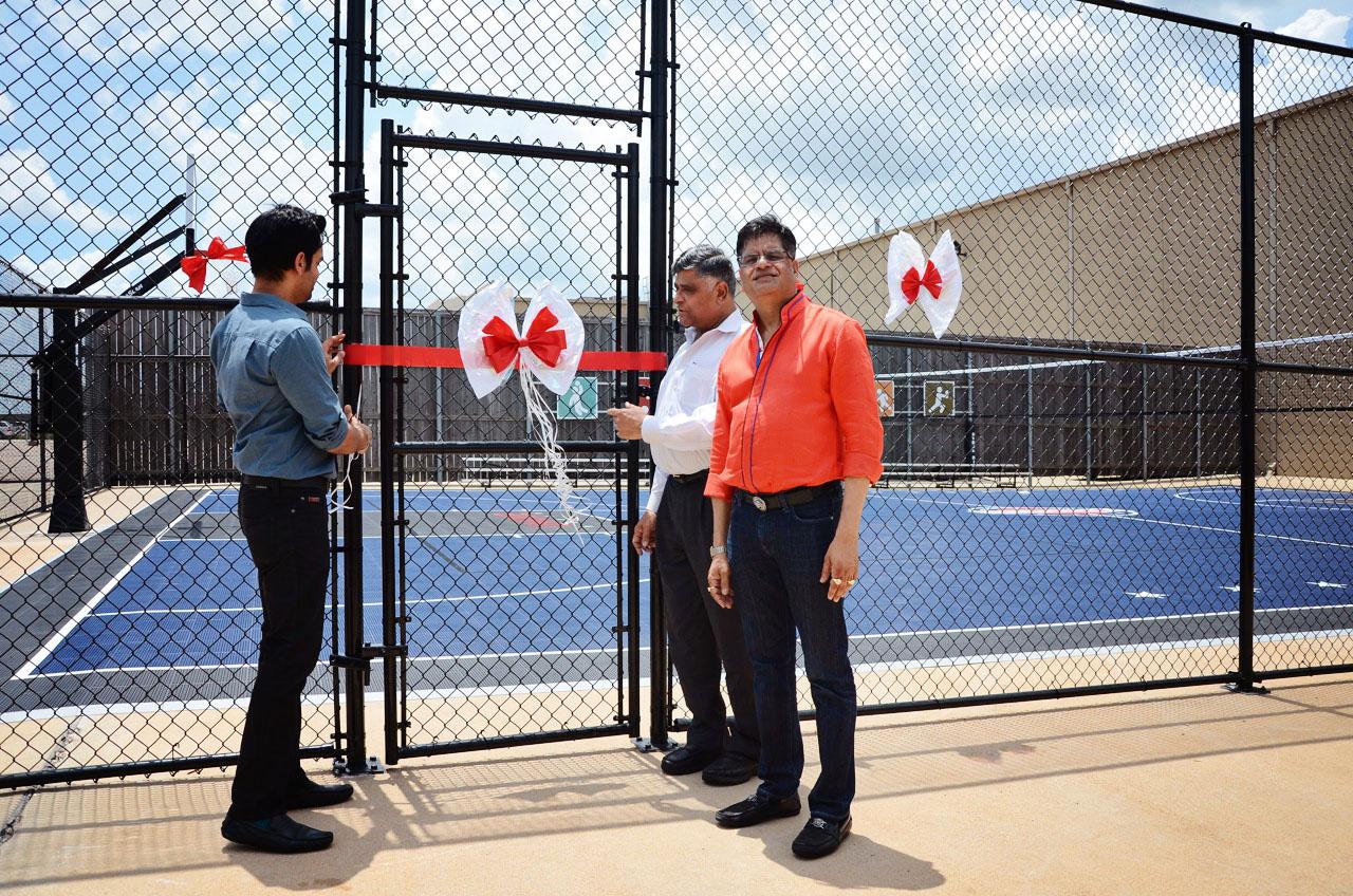 On opening day, from left, Pankaj Malani, Pradeep Gupta and Jugal Malani cut the ribbon on the fenced in court.
