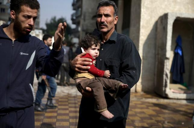 A man carries an injured child as another man gestures at a site hit by missiles fired by Syrian government forces on a busy marketplace in the Douma neighborhood of Damascus, Syria