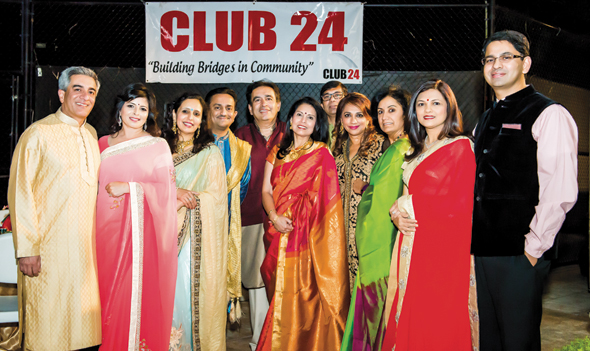 A select group of Club 24 couples pose in front of the Club 24 banner.