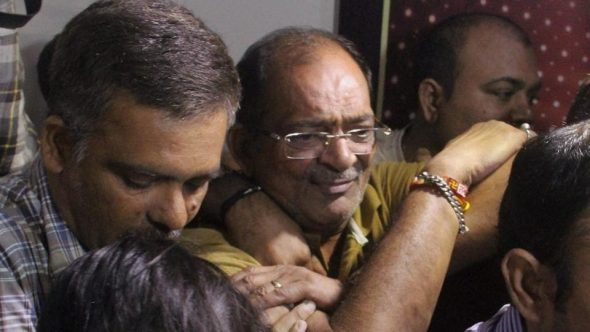 Police and income tax officials with realtor Mahesh Shah, who declared Rs 13,860 crore under the Income Declaration Scheme in Ahmedabad. (PTI Photo)