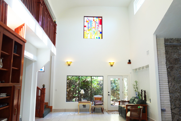 The new vaunted living room with a curved ceiling and stained glass windows reminiscent of Frank Lloyd Wright's designs. The water wall is on the right.