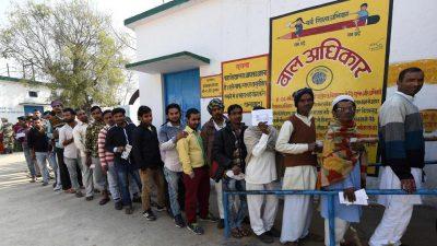 Men wait in a queue to cast their votes at a polling station in Muzaffarnagar in Uttar Pradesh on Saturday.(AFP)