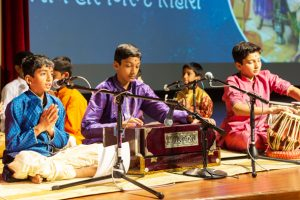 Young children singing kirtans and playing traditional musical instruments