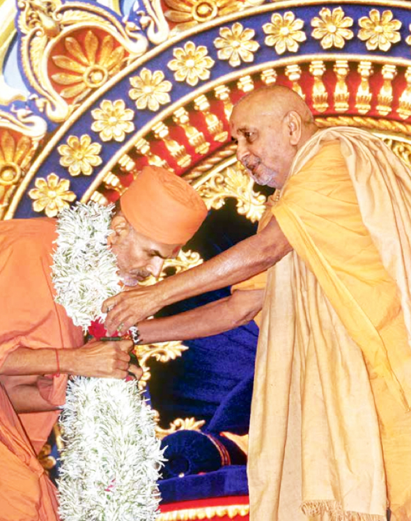 Mahant Swami receiving a garland from Pramukh Swami Maharaj