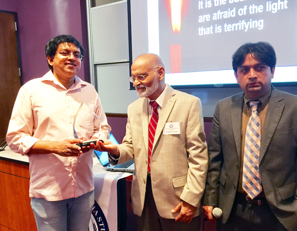 Rationalist campaigner Babu Gogineni (left) receives an award from Foundation for India Studies Chairman Krishna Vavilala (center) with event emcee Vishal Merchant.