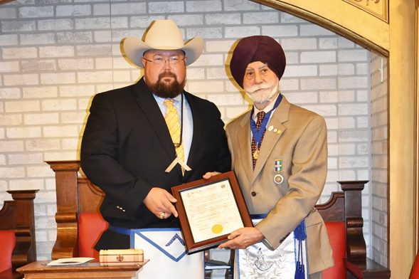 Dr. Raj Bhalla receiving his dedication award from the Worshipful Master Cody Cockroft