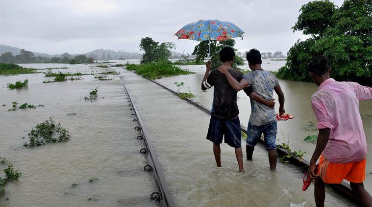 Nagaon: People walking on the flooded railway tracks at Jokhalabandha in Nagaon district of Assam on Monday. PTI Photo (PTI8_14_2017_000110B)