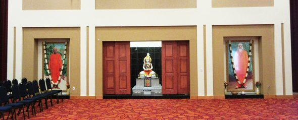 A large stone image Shiva is located off the far side of the auditorium, behind sliding panels, flanked by large framed pictures of Swami Tapovan Maharaj (left) and Swami Chinmayananda (right).
