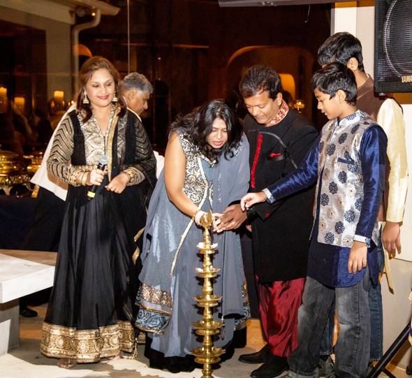 Leena and Ash Shah (center) and their two sons light the traditional Diwali diya to signify the festival of lights under the watchful eye of event co-chair Alpa Shah (left).