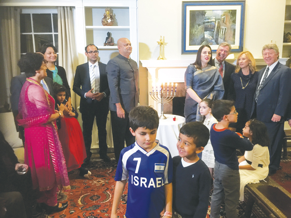 A highlight of the Hanukkah celebration at Consul General of India's home included lighting of the Menorah (candelabra seen at the center) by CG's children and other young guests in the foreground. Seen in the background are Marie Goradia (left), Aparna Ray, Asst. Consul General Surendra Adhana, CG Dr. Anupam Ray, CG's wife Dr. Amit Goldberg Ray, representatives of the American Jewish Congress, Israeli Consulate, and Harris County Judge Ed Emmett.
