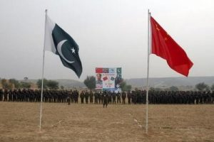 Pakistan and China's national flags fly in the foreground as soldiers from both countries stand together for a group shot after holding joint military exercises in Jhelum, located in Pakistan's Punjab province November 24, 2011. REUTERS/Faisal Mahmood  (PAKISTAN - Tags: POLITICS MILITARY)