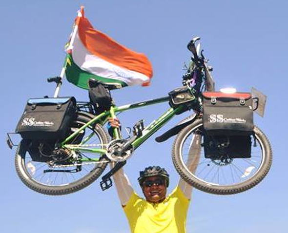 Sharma holding the bike that has served him over thousands of miles across the world.