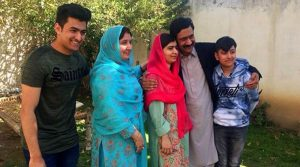 Pakistan's Nobel Peace Prize winner Malala Yousafzai, center, poses for a photograph with her family members at her native home during a visit to Mingora, the main town of Pakistan Swat Valley, Saturday, March 31, 2018. AP