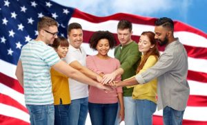 diversity, teamwork, race, ethnicity and people concept - international group of happy smiling men and women holding hands together over american flag background