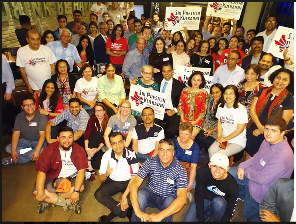 Sri Kulkarni (center) celebrates the landslide win in District 22 runoff with his mother Margaret (left) and room full of volunteers at the victory party in Sugar Land.