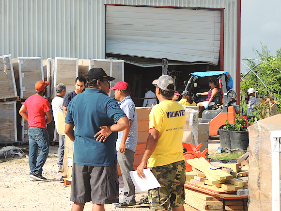 Sewa International's Houston Chapter Coordinator Achalesh Amar (in yellow T-Shirt) supervising the distribution of construction materials to Harvey affected residents in Rosharon, TX.