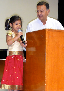 Acarya Gaurang Nanavaty listens to Komal Kallur, youngest toddler of Bala Vihar as she captivate audience.