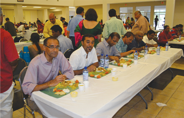 Attendees enjoying the grand feast during the festivities at Sri Meenakshi Temple on Sunday April 28.