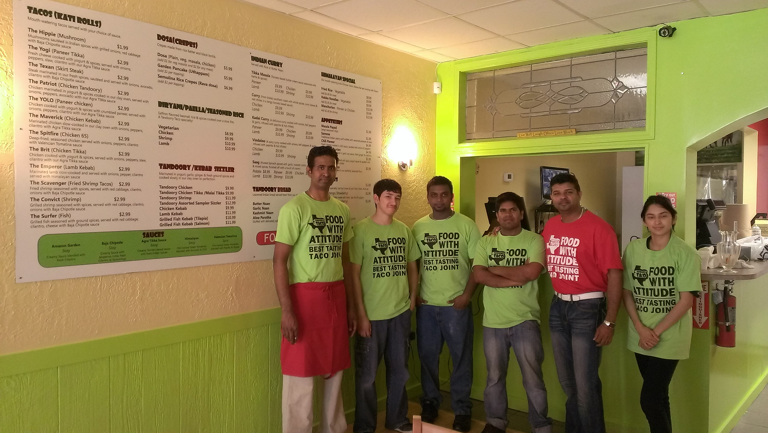 The staff of Tandoory Taco poses next to their menu, the head cook, Kathir Athi (left), Yash Nagalingam (second from right).