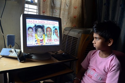 Sanjeev Gupta/European Pressphoto AgencyVishal, a ten-year-old boy looking at photographs of his family members who have gone missing in the floods in Uttarakhand.