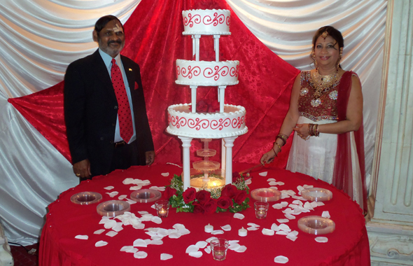 "Sameet ""Sam"" and Indira ""Ann"" Bhushan pose with their four-tiered wedding anniversary cake celebrating 35 years together. The bandages covered a severe allergic reaction Sam suffered after a recent fall.          Photos: Jawahar Malhotra"