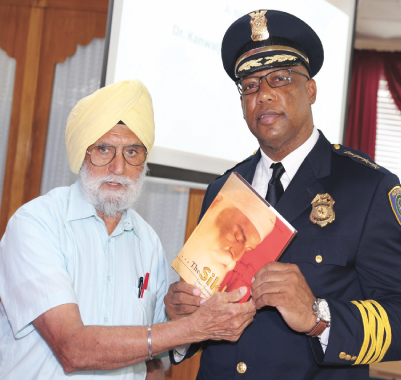 President of the Sikh Center, Kanwaljeet Singh presenting HPD Chief Charles McClleland a book on Sikhism as a token of our appreciation