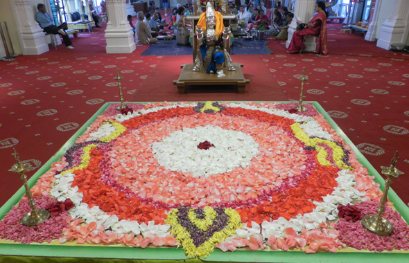 A flower-petal rangoli design in the Rama Temple just before the sanctuary to the main deities. A silver statue of Hanuman stands guard