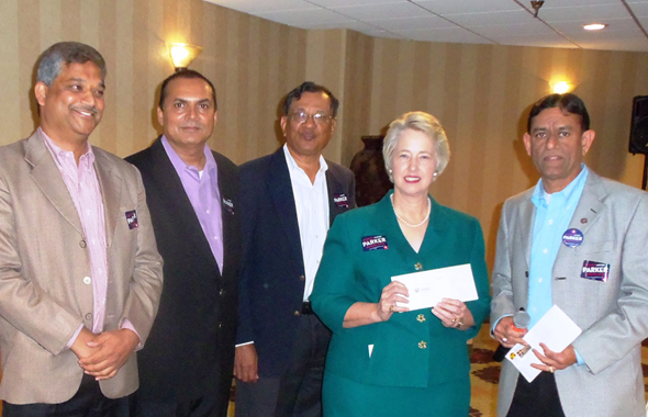 Mayor Annise Parker accepts checks of support from the members of SIMA and IAPAC at the fundraiser last Sunday evening at the Hilton Southwest Hotel. SIMA President Hasu Patel (right) and IAPAC President-elect  Karun Sreerama (second from left) helped organize the event.Photos: Jawahar Malhotra.