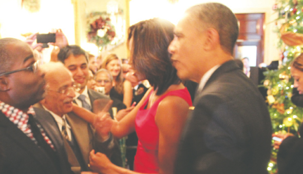 """Lalit Chinoy, with his son Mitren, meeting President Obama and First Lady Michelle Obama at the White House Christmas Party on Friday, December 20. Chinoy is pointing out to Mrs Obama """"that actually she is the President""""."""