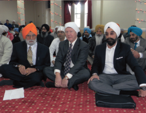 From left: Dr. Kanwaljit Singh, Judge Ed Emmett and Bobby Singh sit among the congregation listening to the lecture by Prof. Gurcharan Singh.