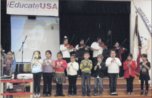Students played two songs on their recorders and violins in homage to David Raj whose photo was projected on the screen behind them.