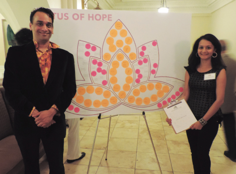 """Anand Ramaswamy and Vyoma Majmudar - Banker stand before the highly successful """"Lotus for Hope"""" donation board during Daya's """"Dine and Disco for Daya Gala 2014."""