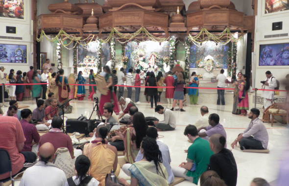 Devotees and the curious filed by the new altar to Radha and Krishna as young, faithful ISKCON followers sang bhajans and danced in the entrance foyer.
