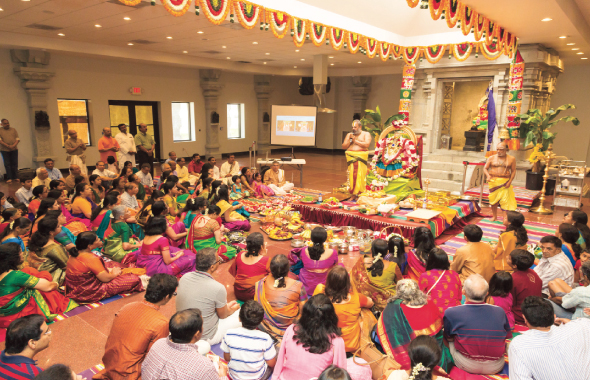 Devotees gathered in the new Ganesh Temple Hall listen intently to the chanting at Lakshmi Pooja.