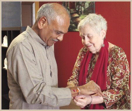 Beth Kulkarni, the founding member of Hindus of Greater Houston, ties rakhi to Sharad Amin,HGH President.