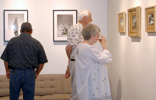 Visitors to the DesignWorks Gallery in Galveston examine Narinder Sall's images.