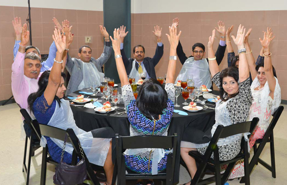"""Guests raised their hands as Lighthouse President Gibson Duterroil said """"Many hands make light work""""        Photos: Bijay Dixit"""