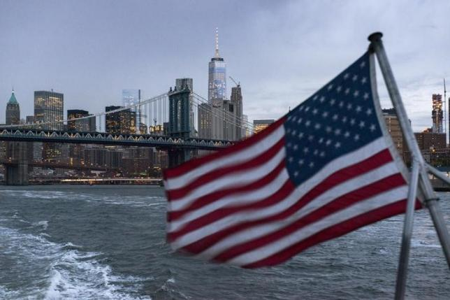 The Lower Manhattan skyline, One World Trade Center and Manhattan Bridge are seen in the background as a ferry with a U.S. flag cruises along the East River while carrying passengers (not pictured) to the 2016 Volkswagen Passat reveal in New York