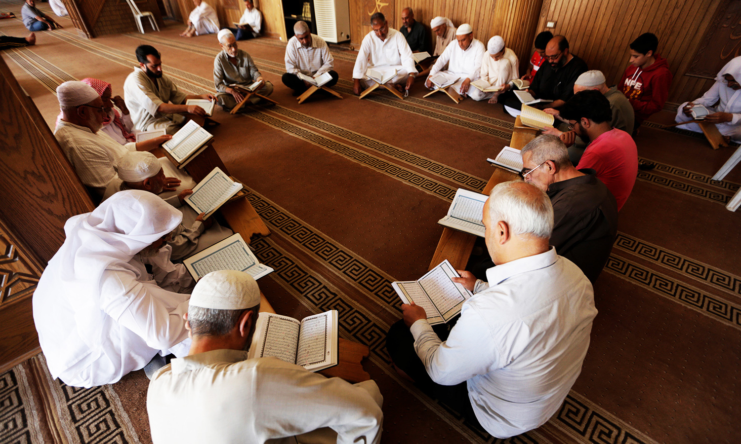Men read the Koran at the Grand mosque during the holy month of Ramadan in the rebel-controlled area of Maaret al-Numan town in Idlib province