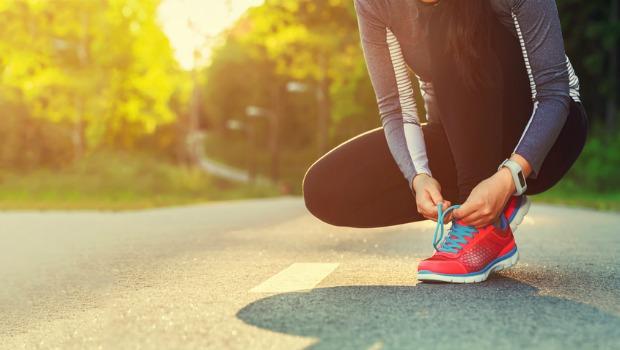 Female runner tying her shoes preparing for a jog