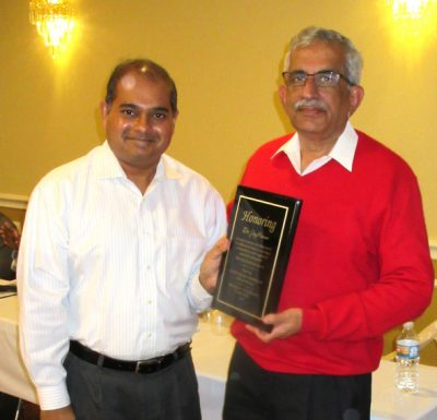 Dr. Manish Gandhi (left) presents an award to Dr. Jay Raman